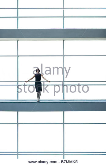 A businesswoman on a walkway of a large modern office building - Stock-Bilder