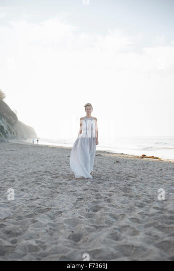Blond woman wearing a long dress standing on a sandy beach. - Stock Image