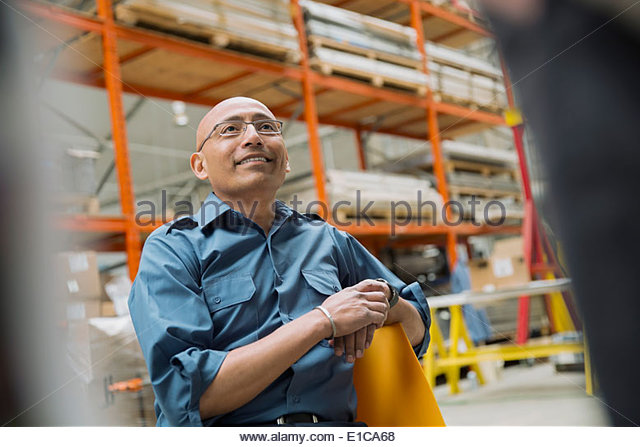 Smiling worker looking up in warehouse - Stock Image