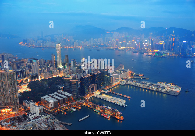 Victoria Harbor aerial view with Hong Kong skyline and urban skyscrapers at night. - Stock Image