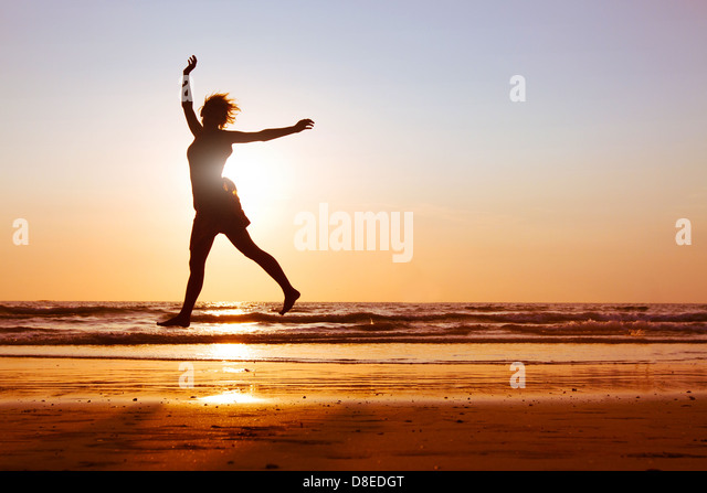 Young happy woman dancing on the beach at sunset with sea background, silhouette - Stock Image