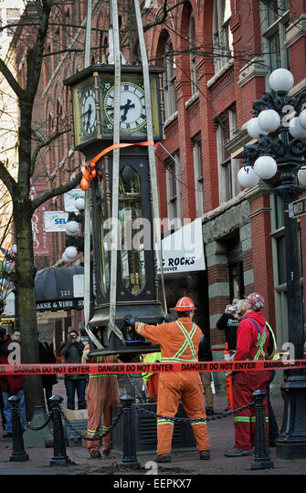 Canada, Vancouver. 21st Jan, 2015. Workers re-install the steam clock to its original position at Gastown in Vancouver, - Stock Image