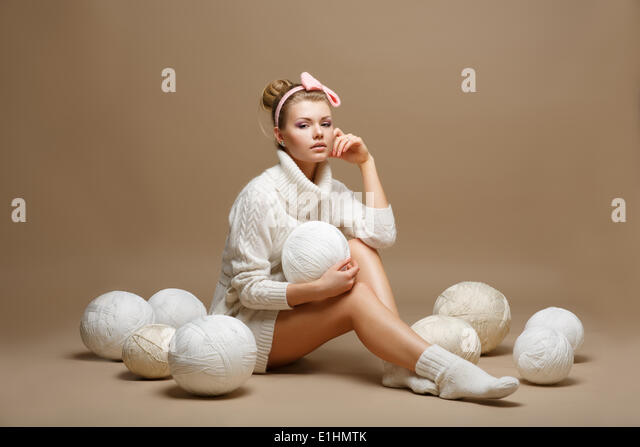 Housework. Young Woman in White Tricot with Woolen Balls. Seamstress - Stock Image