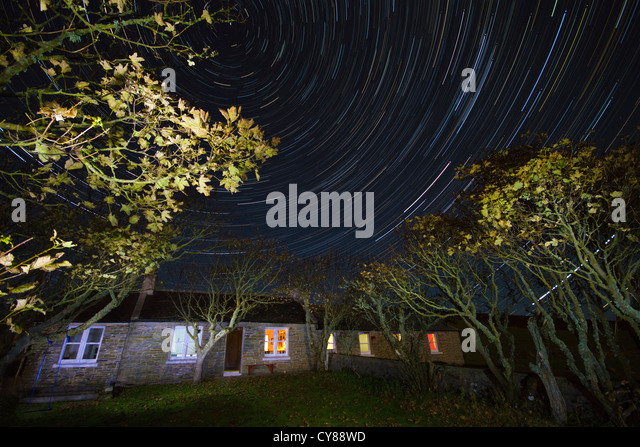 Rural cottage with star trails - Stock Image