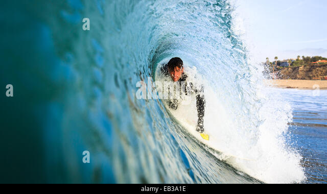 USA, California, Los Angeles County, Malibu, Young man surfing under curve of barreling wave - Stock-Bilder