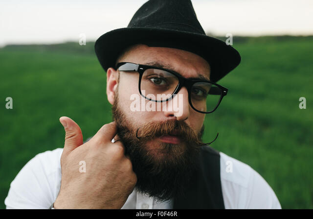 man with a beard, thinking in the field - Stock-Bilder