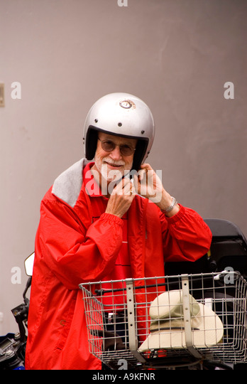 Bermuda elderly older old man in red rain coat helmet beside motor scooter - Stock Image