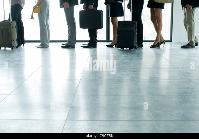 People standing in line, low section - Stock Image