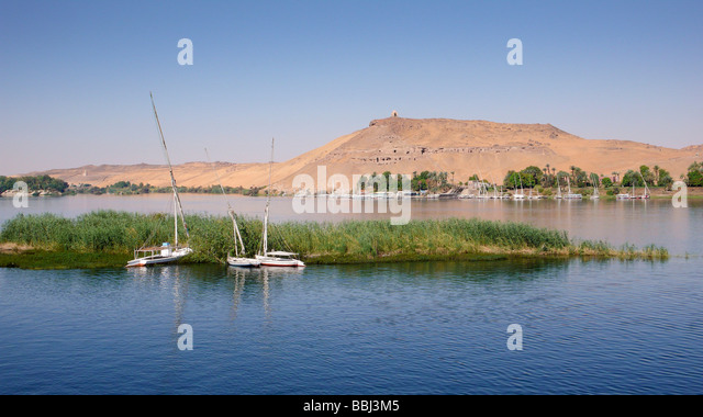 Nile at Aswan, in the back rock tombs, Egypt, Africa - Stock Image