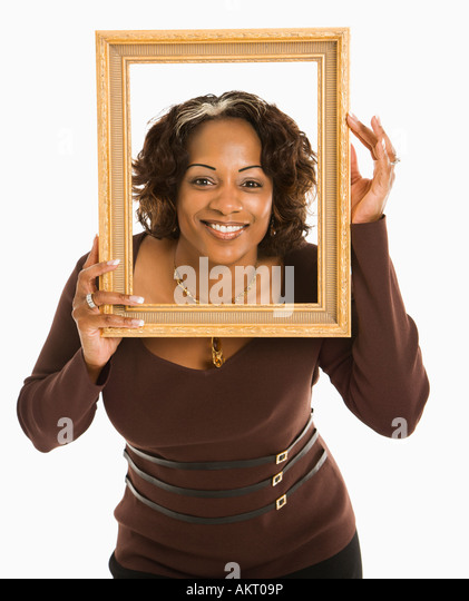 Woman holding empty frame around head smiling - Stock Image