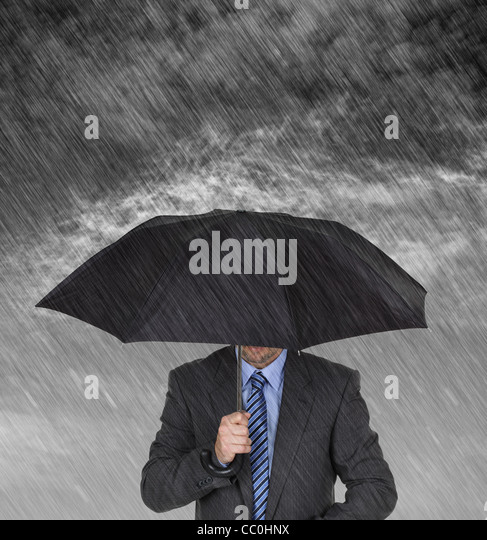 Businessman sheltering from the rain - Stock Image