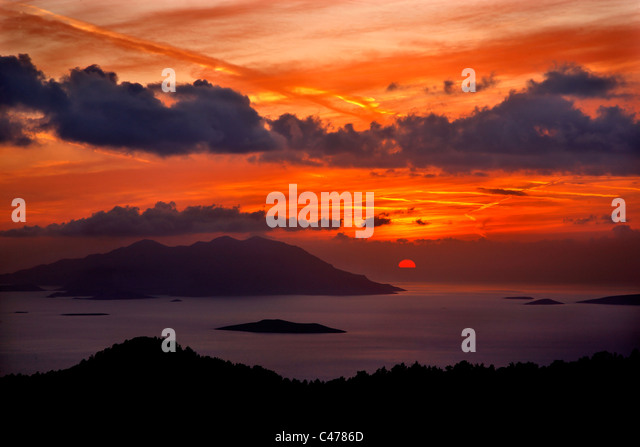 Sunset photo from southwest Rhodes, close to Kritinia village. The large island in the background is Chalki. Dodecanese, - Stock Image