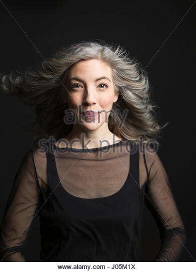Portrait wind blowing gray hair of confident woman against black background - Stock Image