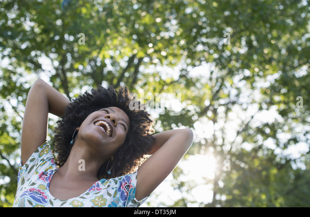 A young woman in a flowered summer dress with her hands behind her head smiling and looking up - Stock Image