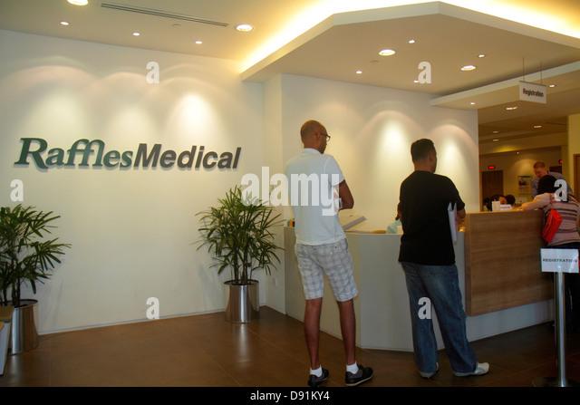 Singapore Bugis Raffles Medical Raffles Hospital lobby Asian man registration - Stock Image