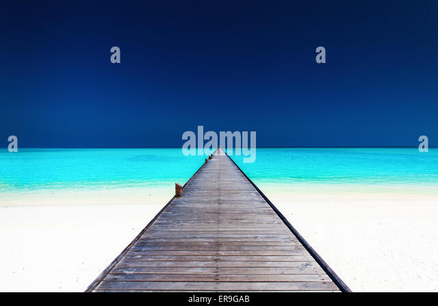 Wooden long jetty over lagoon with amazing clean azure water - Stock Image