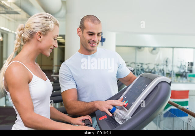 Trainer assisting woman with treadmill screen options at gym - Stock Image