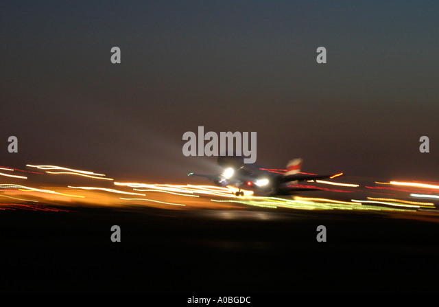 Airliner taking off at night London Heathrow Airport England UK - Stock Image