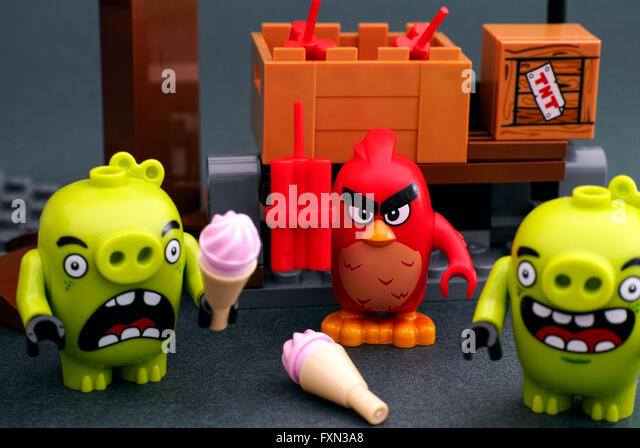 Tambov, Russian Federation - April 14, 2016 Lego Angry Birds. Red bird with dynamite stands behind 2 bad piggies - Stock Image