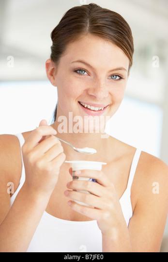 Young Woman Eating Yogurt - Stock Image