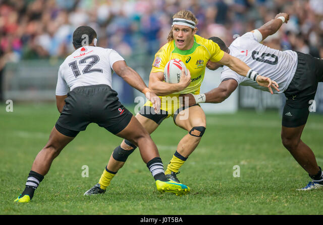 Fiji's Tom Lucas (Australia, 10) in action against Vatemo Ravouvou (Fiji, 12) and Mesulame Kunavula (Fiji, 6) - Stock Image