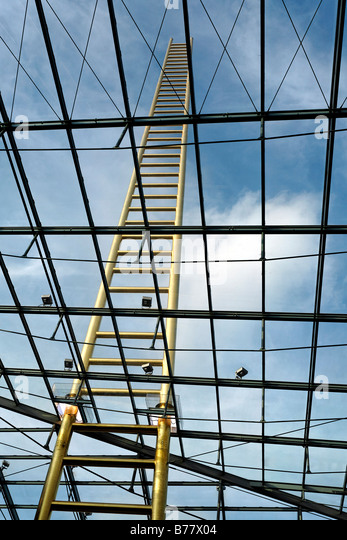 Golden ladder soaring into the sky, through glass roof, artistic landmark of the new Forum Duisburg Shopping Centre, - Stock Image