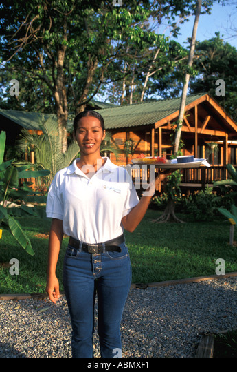 Honduras Pico Bonito Lodge Vertical Woman serving breakfast outside lodge MR 350 - Stock Image