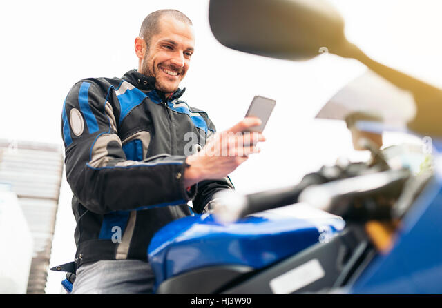 Handsome biker using mobile phone in the street. - Stock Image
