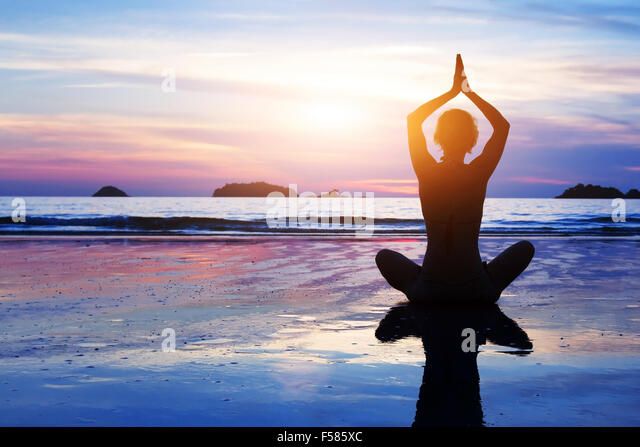 yoga background, abstract silhouette of woman meditating on the beach - Stock Image