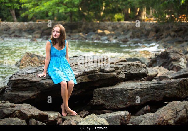 Teen-girl in a blue dress in the rocks of the coast. - Stock Image