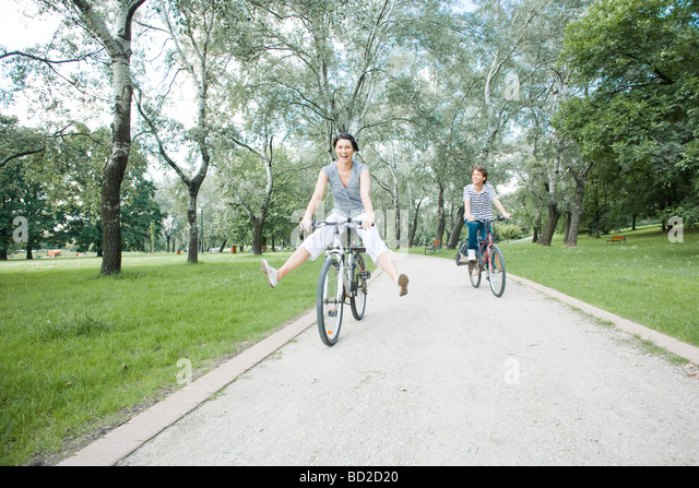 Couple riding on bicycles in park - Stock Image