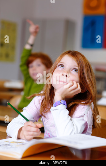 Children in a classroom in primary school, girl looking clever, cunning and knowledgable, equal oppurtunity in the - Stock Image