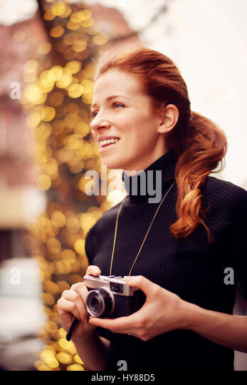 Young fashionable women with classic camera in front of lights in New York city - Stock Image