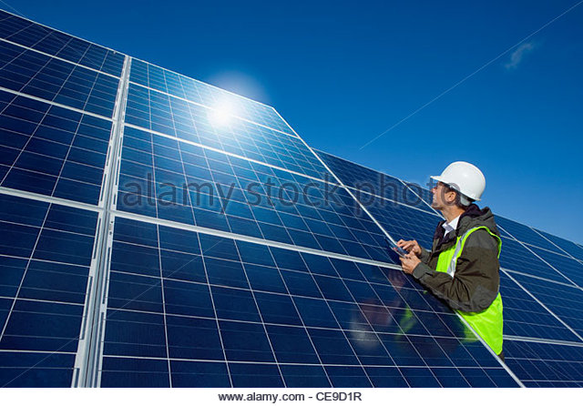 Engineer with digital tablet inspecting solar panels - Stock Image