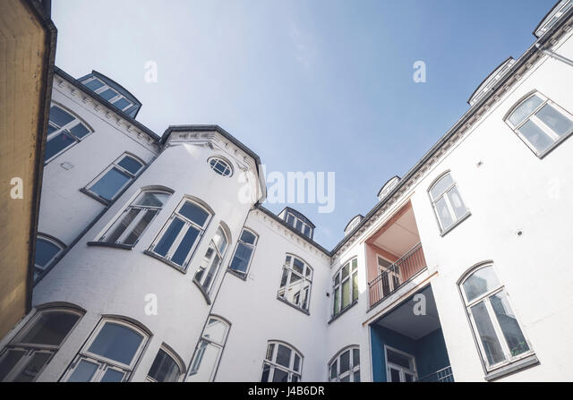 Apartment building in white color with many windows and balconys in daylight with blue sky - Stock Image