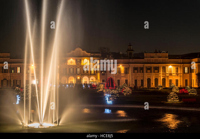 Fountain in the foreground and Christmas lights in the public gardens of Varese - Stock Image