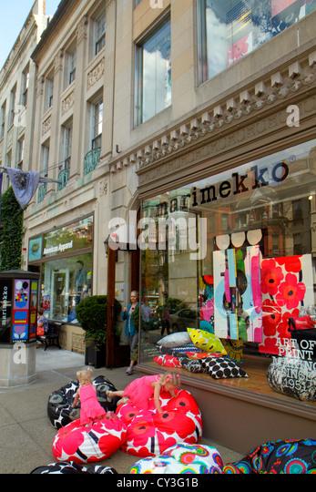 Boston Massachusetts Back Bay Newbury Street high-end luxury name-brand shopping girl playing bean bag chair Marimekko - Stock Image