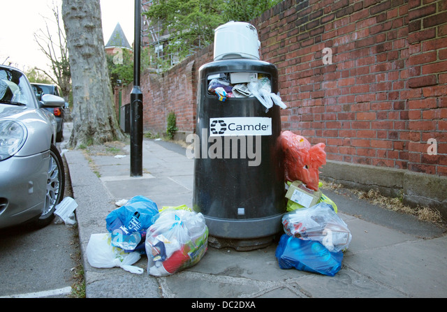 Overflowing rubbish bins on a residential street in London uk - Stock Image