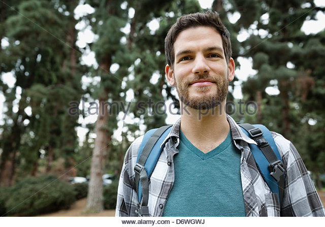 Portrait of handsome mid adult man with backpack in forest - Stock Image