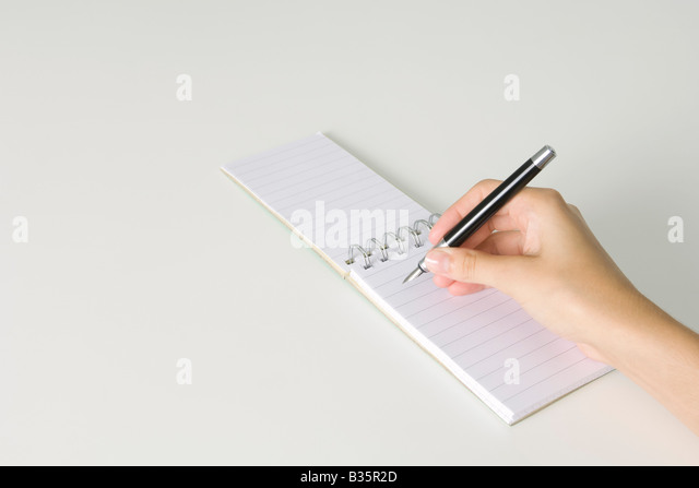 Hand holding pen, poised to write in notepad flipped open, cropped view - Stock-Bilder