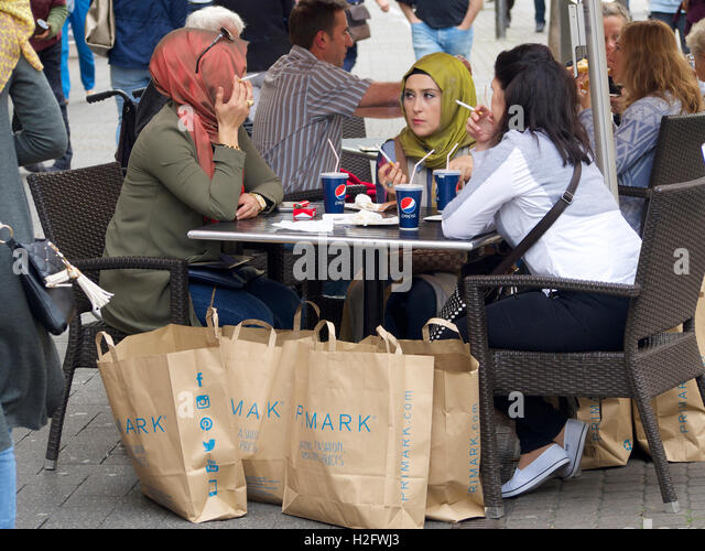 Female muslim friends, smoking and haveing a Pepsi, that have been shopping at Primark in Cologne, Germany - Stock Image