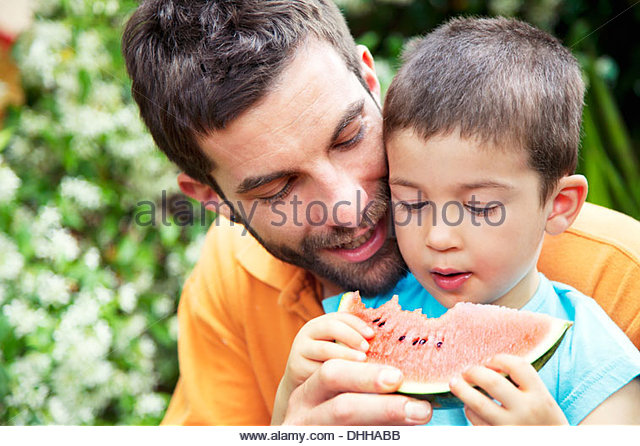 Father holding slice of watermelon, son eating it - Stock Image