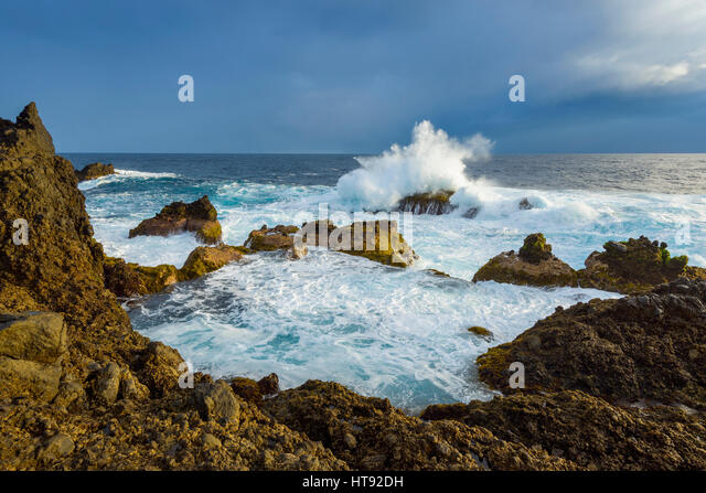 Lava Rock Coast at Sunrise with Breaking Waves, Charco del Viento, La Guancha, Tenerife, Canary Islands, Spain - Stock Image