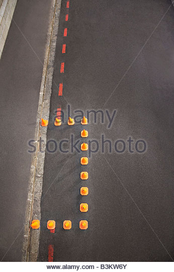 Traffic cones blocking off part of urban street - Stock Image