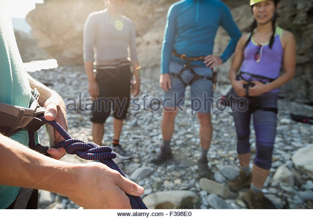 Rock climber adjusting rope knot - Stock Image
