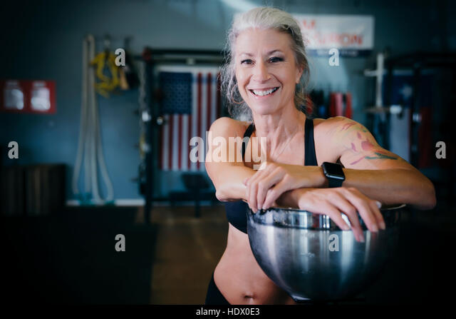 Smiling Caucasian woman leaning on bowl in gymnasium - Stock Image