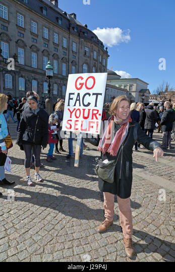 Woman holding GO FACT YOURSELF placard on Chrisriansborg Castle Square in Copenhagen after the March for Science - Stock Image