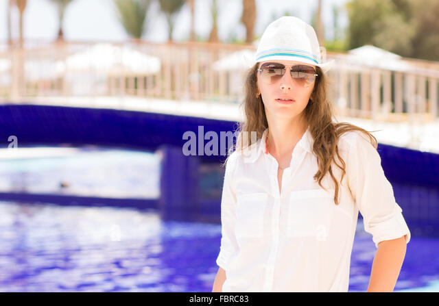 Young beautiful girl stands near the swimming pool. Pretty woman on summer holidays at tropical resort - Stock-Bilder