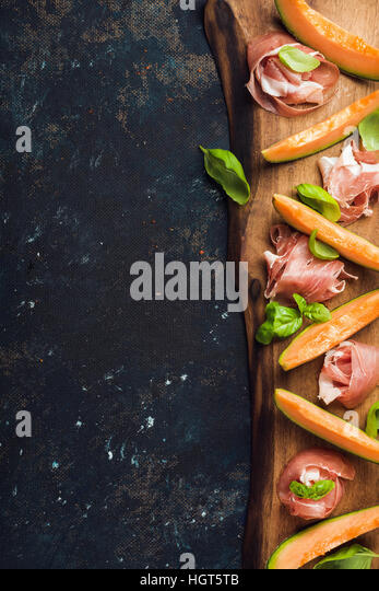 Prosciutto with cantaloupe melon and basil leaves on wooden board - Stock Image