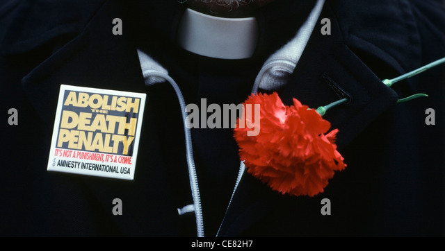 Anglican Priest wearing  Amnesty International pin and a red carnation before a anti-death penalty demonstration - Stock Image